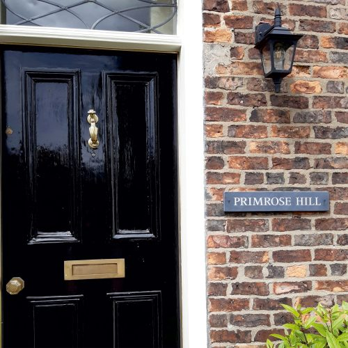 Example of a Blue Grey Welsh Slate House Sign. House Name in all Roman Capital letters & Painted White, placed on a brick wall